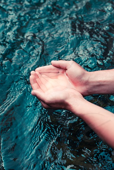 Young boy taking pure water from a river and holding it in the hands. Closeup of hands holding a clean water photo