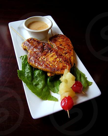 Chicken satay on white rectangular plate with peanut sauce photo