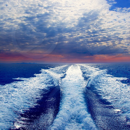 Blue sea with prop wash wake and Ibiza Island in horizon on sunrise photo