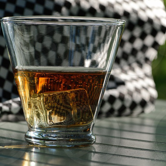 Glass of whiskey on ice checkered racing flag background photo