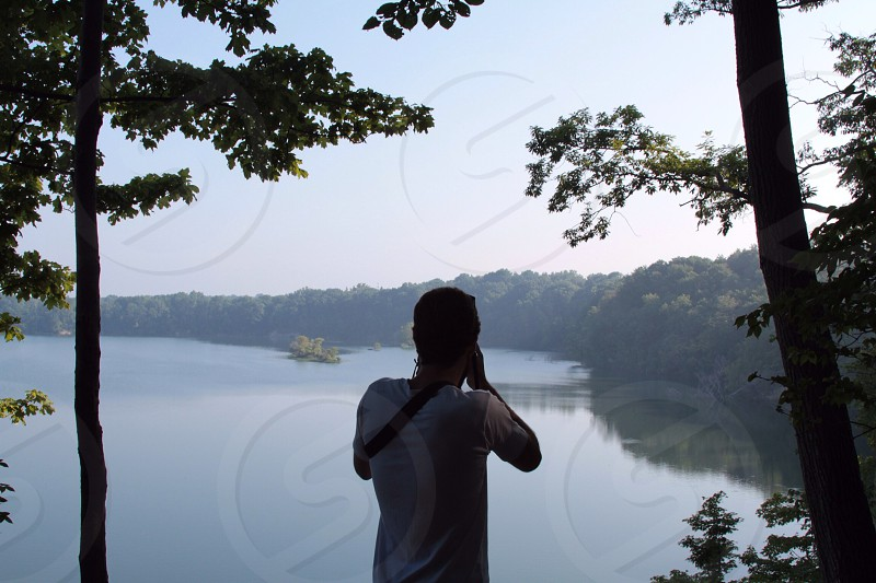 man in white t shirt standing between 2 tall trees and taking pictures of lake photo