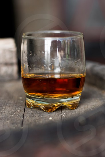Glass of whiskey on wooden barrel photo