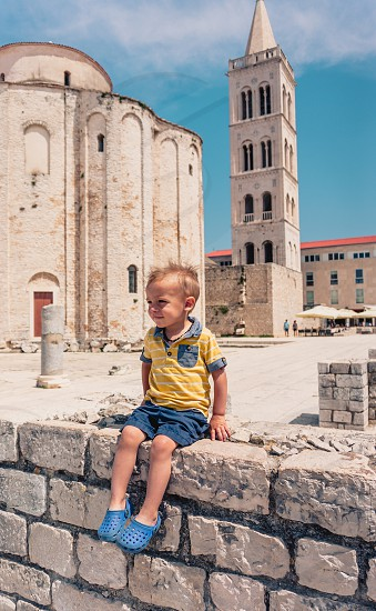 Toddler boy sitting on wall in Croatia photo