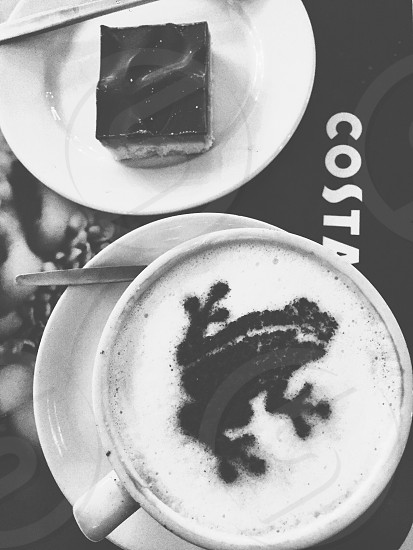 grey scale photo of white ceramic mug with coffee and white frothy and black frog style powder on top of it photo