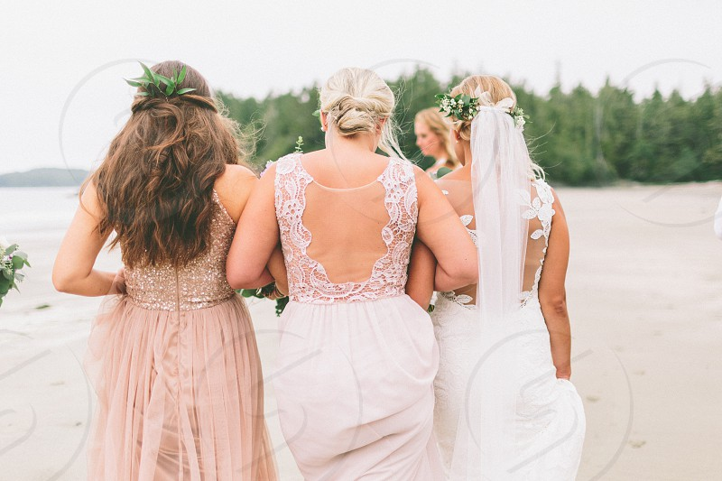 A bride and her bridesmaids walking along a beach.  photo
