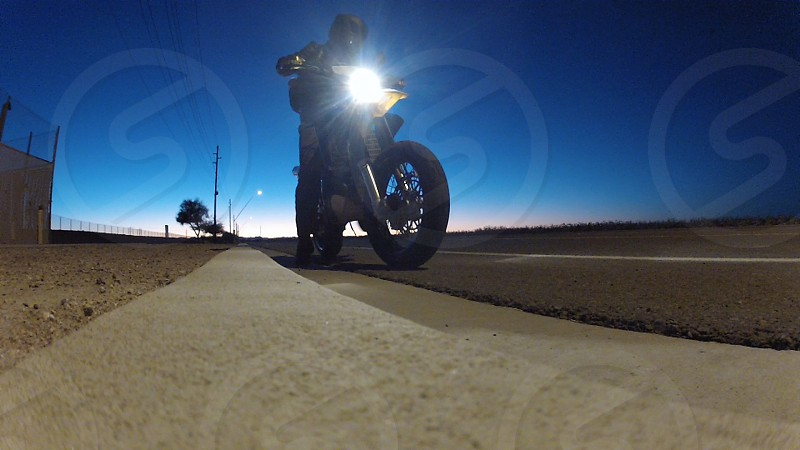 Riding the motorcycle on a quiet road at dusk.  photo