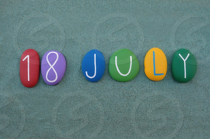 18 July calendar date composed with multi colored stones over green sand photo