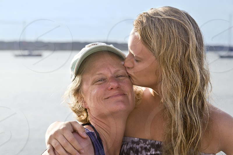 woman kissing her mother near the sea during daytime photo
