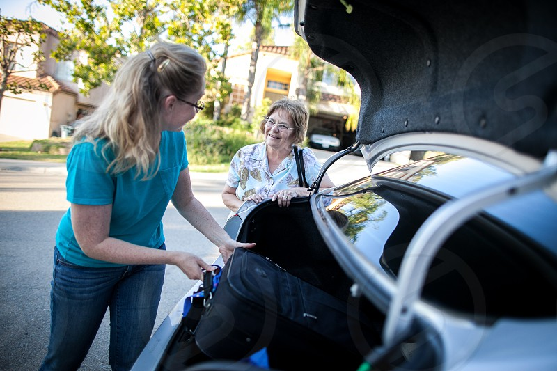 A young woman in a turquoise T-shirt and jeans helps a lady load a black suitcase into the open trunk of a silver sedan on a suburban neighborhood curbside - both smiling and happy. photo