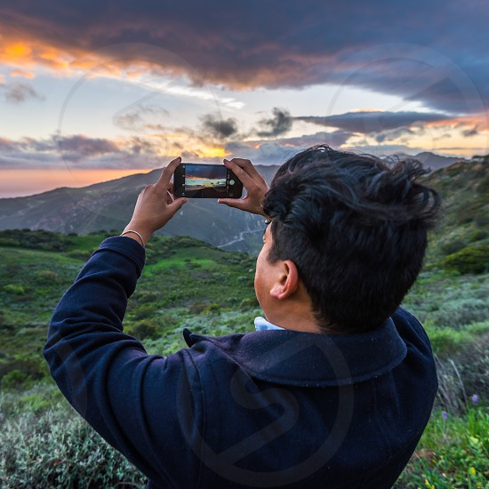 man in black jacket holding space grey iphone 6 and taking picture of orange sunset on mountain photo