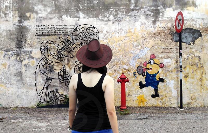 woman in black tank top facing minion graffiti photo