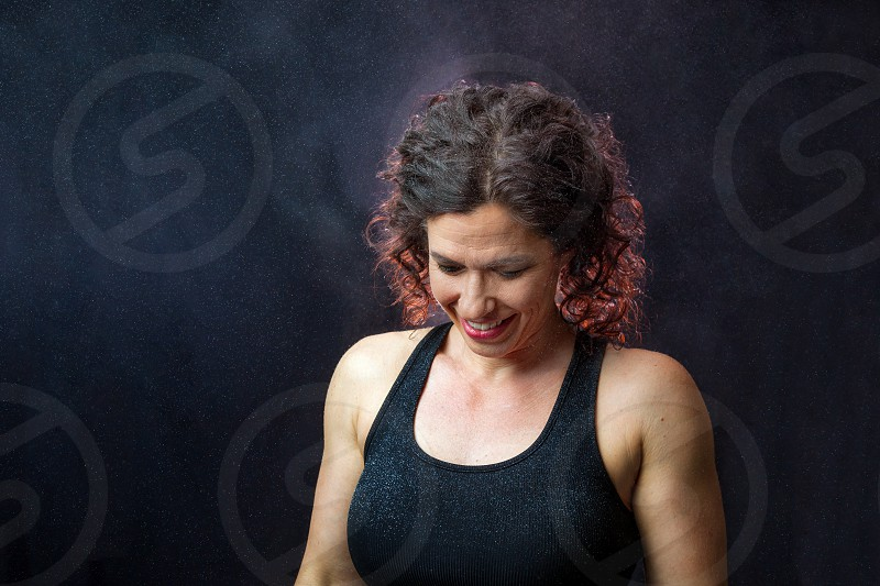 A muscular female trainer with curly hair looks down and smiles.  The background is black and she is backlit with particles and clouds of chalk dust all over her and in the air. photo