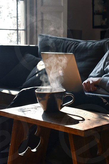 Using a laptop computer while relaxing on the sofa on a sunny day. photo
