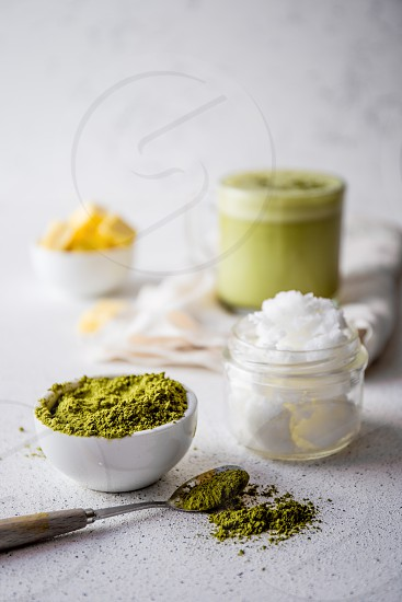BULLETPROOF MATCHA. Ketogenic keto diet hot drink. Tea matcha blended with coconut oil and butter. Cup of bulletproof matcha and ingredients on white background. photo
