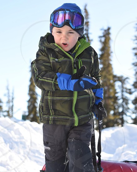 Child snow tubing and skiing photo