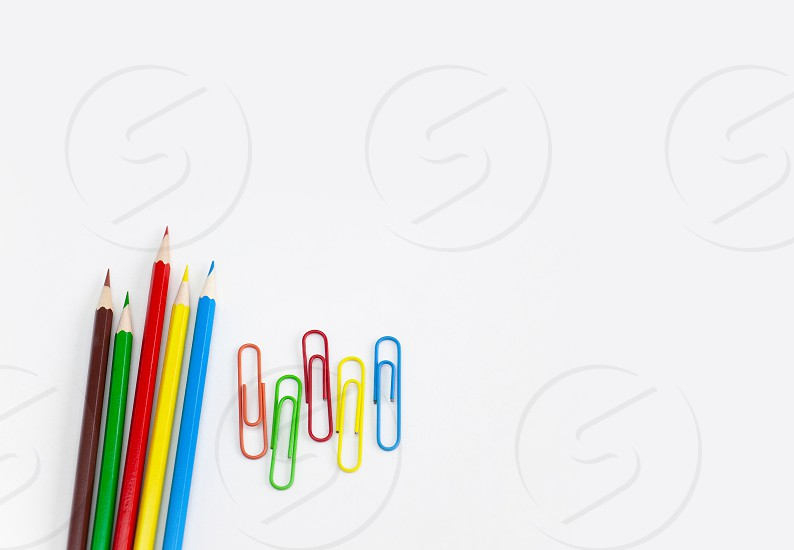 School supplies stationery concepts Multi-colored pencils and clips on white background with copy space. View from above. photo