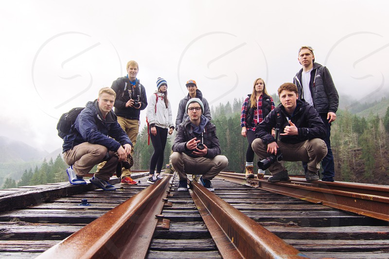 men and women in puffer coats on railroad tracks photo