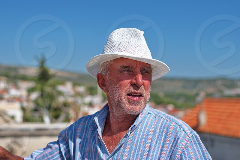 Waist up portrait of a senior man with a hat with cityscape of Primosten in Croatia in the background photo