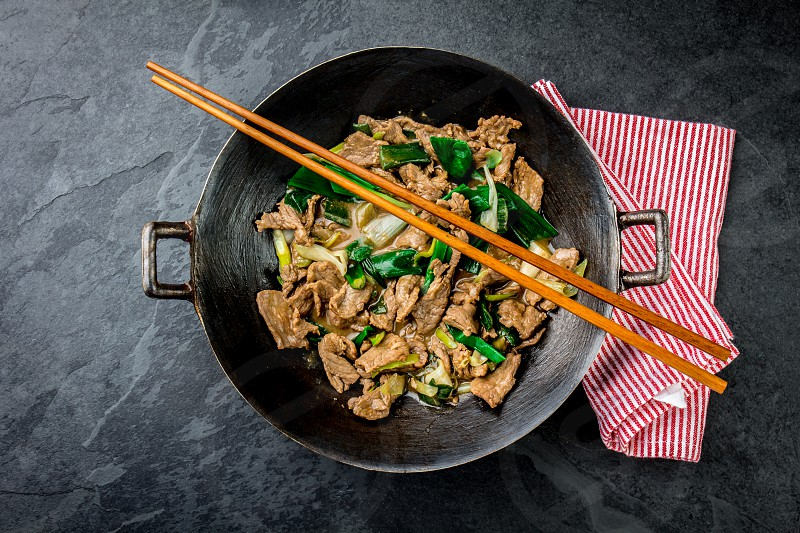 Traditional chinese mongolian beef stir fry in chinese cast iron wok with cooking chopsticks stone slate background. Top view copy space. photo