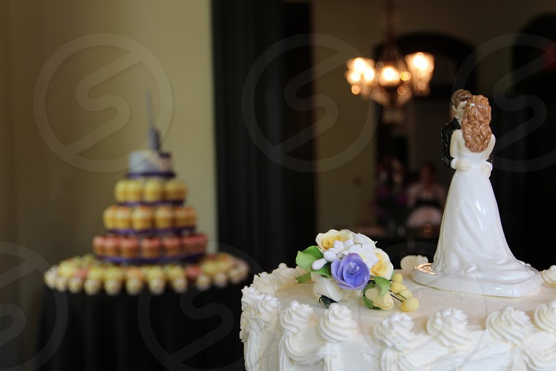 Bride and groom cake topper wedding cake with cupcake tower in background photo