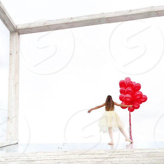woman in white dress holding red balloons photo