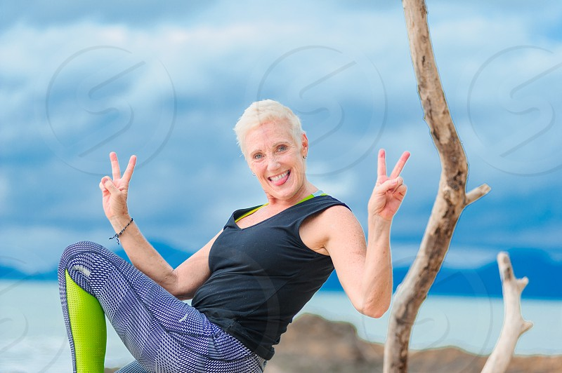 Beautiful mature aged woman doing yoga on a deserted tropical beach. photo
