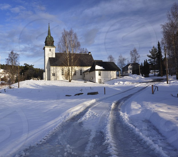 white painted chapel with black roof on snow covered field during day photo