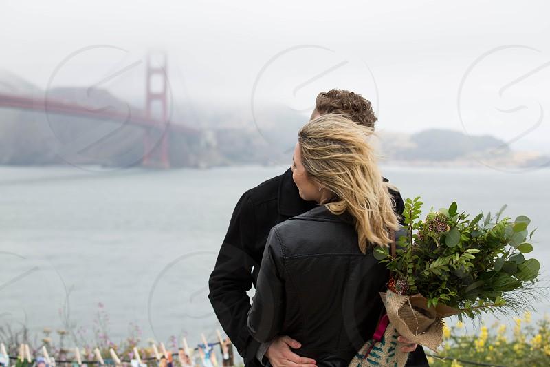 couple flowers golden gate bridge sf san francisco ocean relationship hair wind cold happy photo