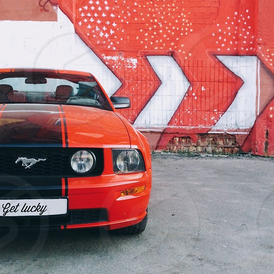 red and black ford mustang parked near concrete building during daytime photo