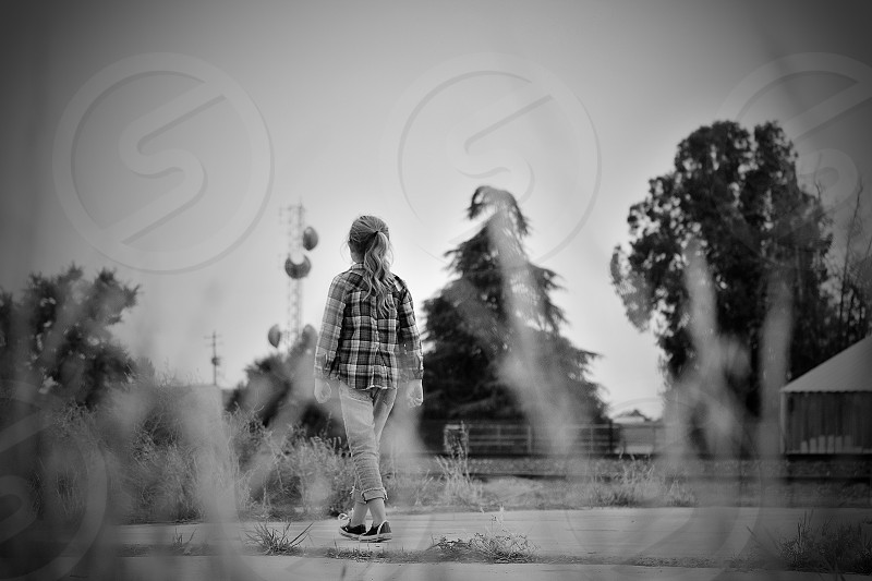 girl in black and white plaid button up shirt walking photo