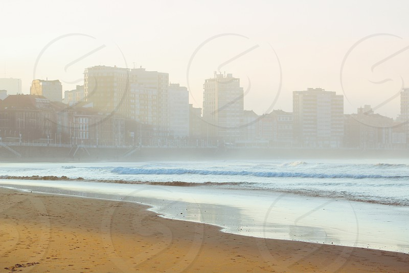 Cityscape of Gijón from the beach of San Lorenzo at sunset. photo