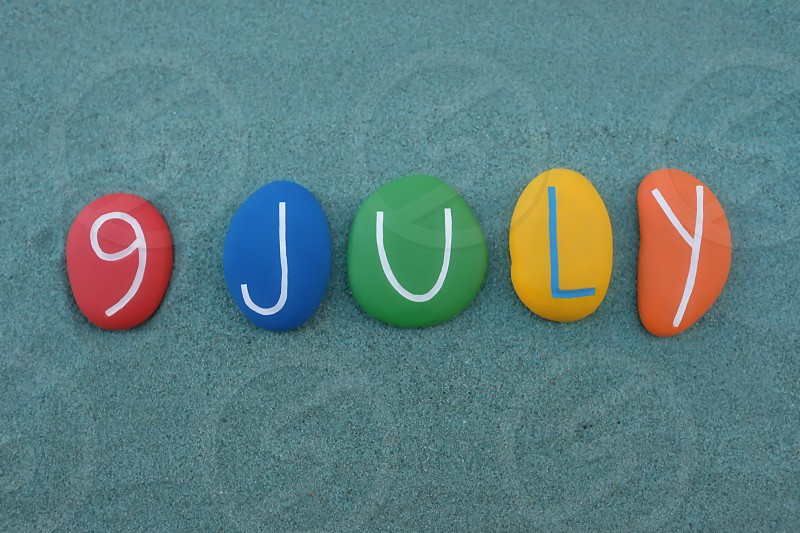 9 July calendar date composed with multi colored stones over green sand photo