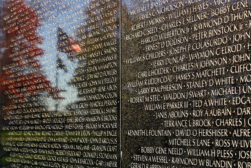 Am American flag is reflected among the names on a portion of Vietnam War Memorial:'The Wall.' photo