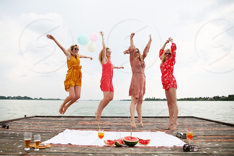 Girl friends trying to jump all together in same time photo