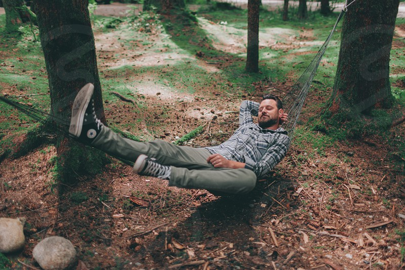 A man relaxing in a hammock in the forest. photo