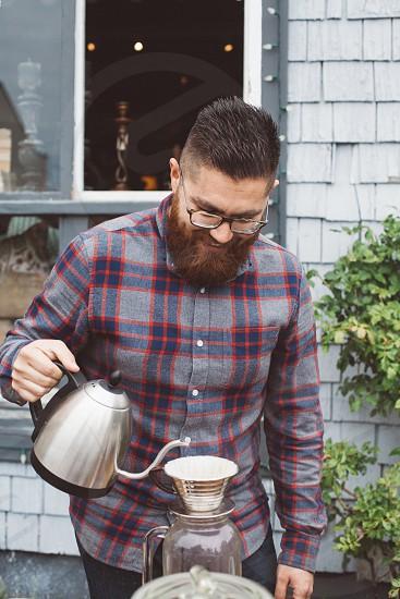 man with plaid shirt pouring liquid photo