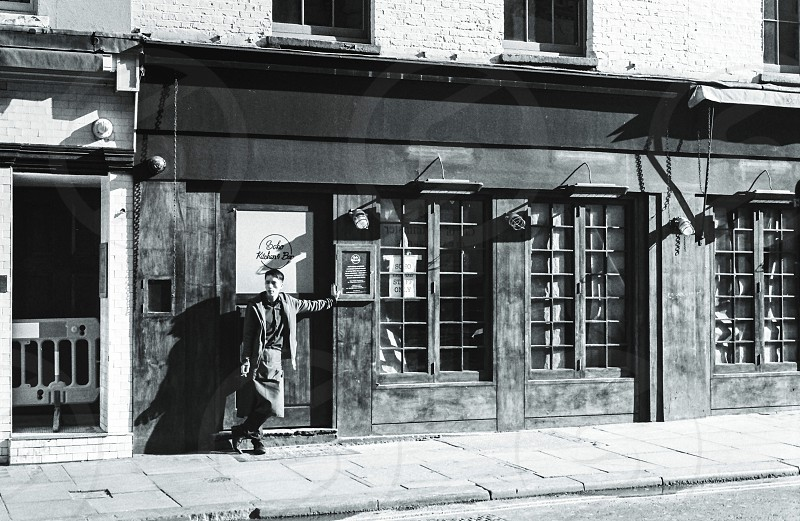 gray scale photography of man standing in front of store during daytime picture photo