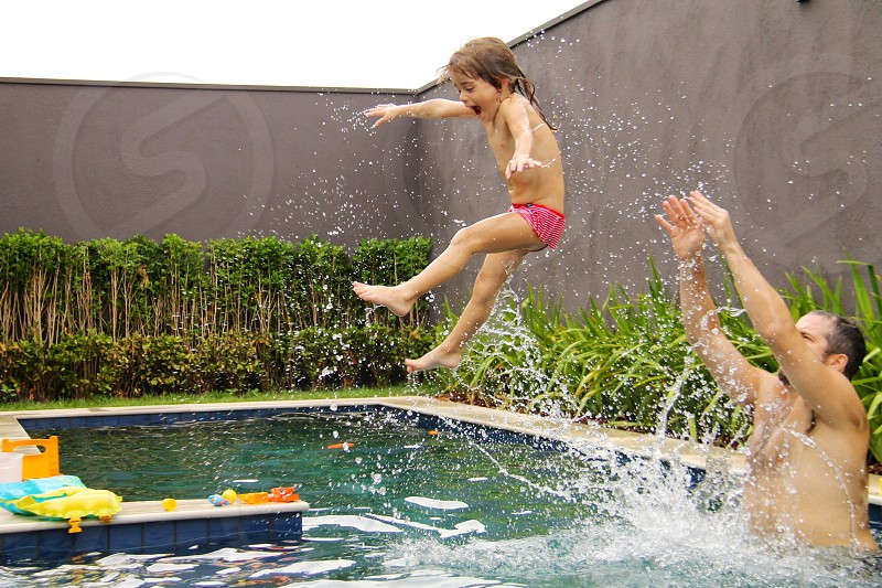 child being thrown by man in pool photo