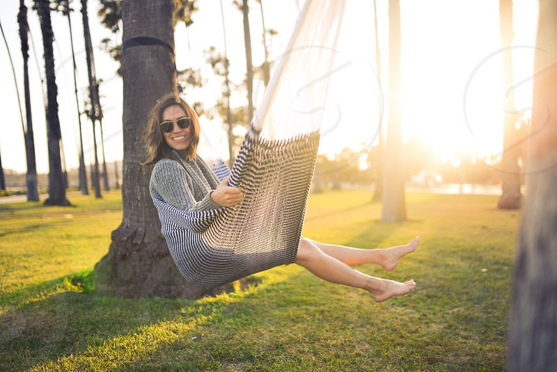 Happy woman looking at camera sitting in hammock photo