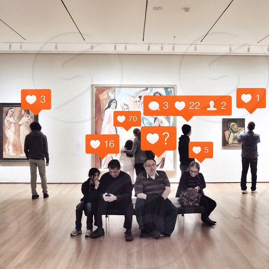 people sitting and standing in museum with paintings photo