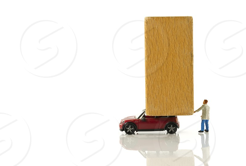 big wooden block on small red car as icon for transport by man photo