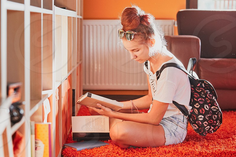 Teenage girl looking for books in local library. Young woman with a backpack sitting by a bookshelf indoors. Real people authentic situations photo