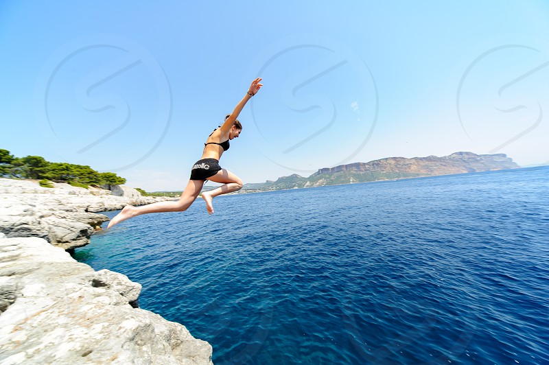 Young Girl jumping into the mediterranean sea Cassis South of France photo
