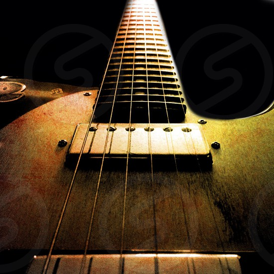brown wooden guitar with silver string photo