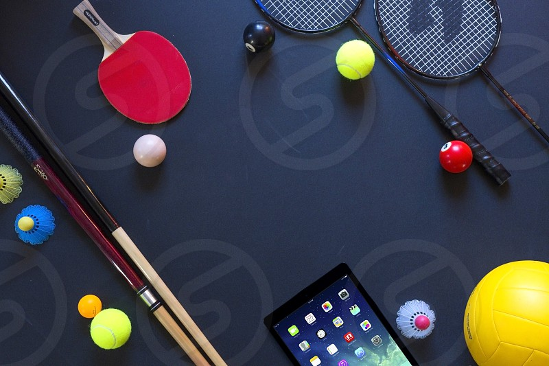 sports objects neatly placed on a black background ipad mini badminton table tennis ping pong cue sticks pool volley ball cue balls ipad mini home screen top view photo