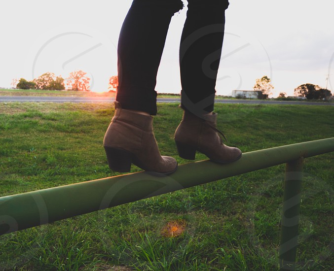 close up photography of a woman in boots walking on metal bar fence photo