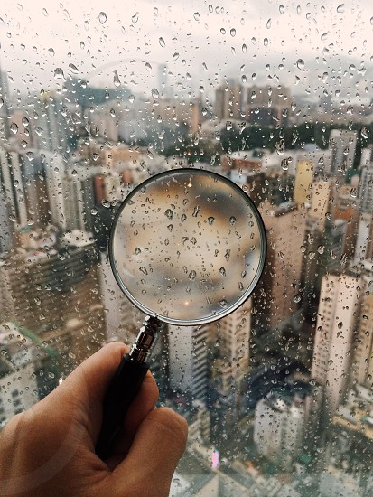 magnifying glass near a rainy window photo
