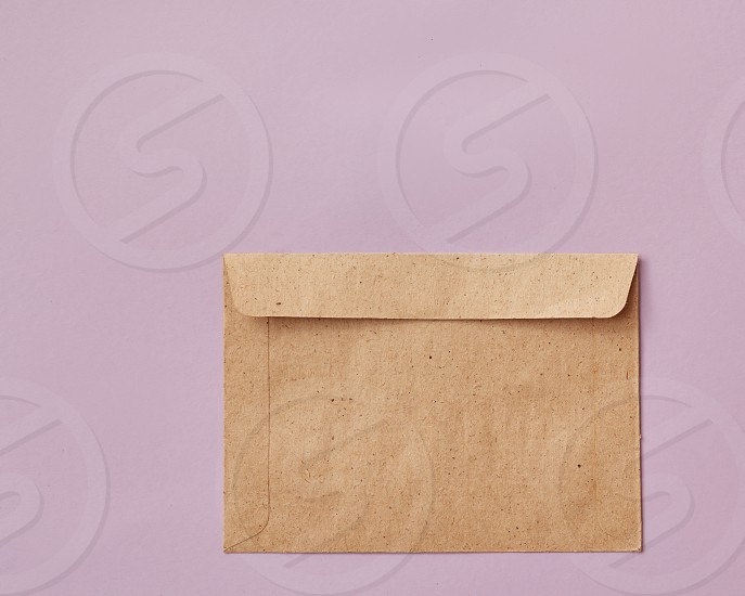 Brown envelopes cardboard sheet of recycle paper gift cards and invitations or business concept with copy space isolated on pink background. Flat lay photo