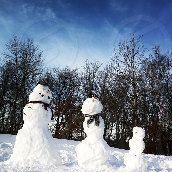 2 snow mans near tree photo