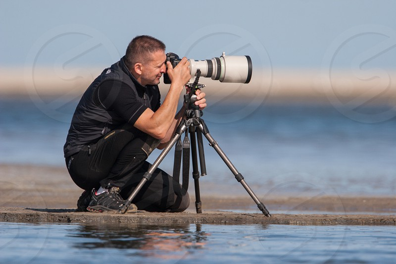Man on the beach in black sportswear photographing surfers with big lens on tripod photo